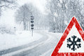 Snowy curvy road with traffic sign sudden and heavy snowfall on a country driving on it becomes dangerous … Stock Photography