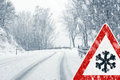 Snowy curvy road with traffic sign sudden and heavy snowfall on a country driving on it becomes dangerous … Royalty Free Stock Image