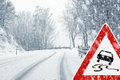 Snowy curvy road with traffic sign sudden and heavy snowfall on a country driving on it becomes dangerous … Royalty Free Stock Images