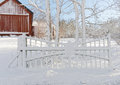 Snowy gate and red barn in the background a winter day Royalty Free Stock Photo