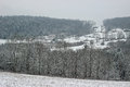 Snowy hilltop a snow covered rural with snow covered trees and houses Stock Photography