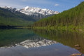 A snowy mountain reflection this image of the of the in the water was taken at stanton lake in the great bear wilderness of nw Stock Image