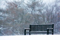Snowy park bench a winter scene with a black in the snow Royalty Free Stock Photo