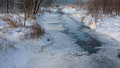 Snowy partly frozen river in morning crossing riparian stand Stock Image