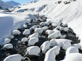 Snowy river andermat switzerland snow capped stones litter a high mountain stream in Royalty Free Stock Photography