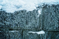 Snowy stony wall with white frost on surface Royalty Free Stock Photo