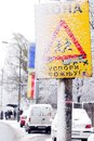 Snowy street sign in belgrade serbian traffic warning slow down parked cars and bus station with people at snow on Royalty Free Stock Photography