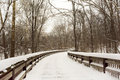 Snowy winter boardwalk scene with a winding wooden crossing a stream in a wooded park Royalty Free Stock Image