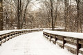 Snowy winter boardwalk scene with a winding wooden crossing a stream in a wooded park Stock Image