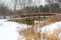 Snowy winter bridge scene with a decorative wooden crossing a stream Stock Photography