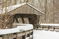 Snowy winter covered bridge painting scene with falling snow and a winding wooden boardwalk leading to a that crosses a river in a Stock Photography