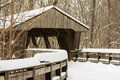 Snowy winter covered bridge painting scene with a winding wooden boardwalk leading to a that crosses a river in a wooded park this Royalty Free Stock Photo