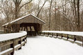 Snowy winter covered bridge scene with a winding wooden boardwalk leading to a that crosses a river in a wooded park Royalty Free Stock Photos