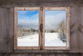 Snowy winter landscape. View out of an old rustic wooden window. Royalty Free Stock Photo
