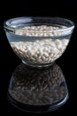 Soaked beans on black with reflection white in water in a glass bowl background Royalty Free Stock Image
