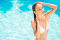 Soaking up the sun rays top view of gorgeous young woman in white bikini standing at pool and keeping eyes closed Stock Images