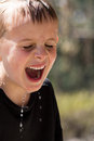 Soaking wet young boy laughing hysterically Royalty Free Stock Image