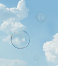 Soap bubbles floating against clear sunlit blue sky and clouds Stock Photo