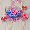 Soap in form of roses in bowl of water on wooden background. Royalty Free Stock Photo