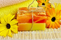 Soap homemade with calendula two bars of towels marigold flowers on a background of bamboo napkins Stock Photo