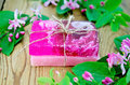 Soap homemade pink with flowers of honeysuckle two bars tied twine twigs leaves and on a background wooden boards Royalty Free Stock Image