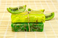 Soap homemade with twine and kiwi two green tied slices on a bamboo mat Royalty Free Stock Photography