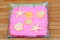 Soaps with shapes of shells and starfish on pink bath salts in a Stock Image