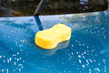 Soapy sponge on the hood of a blue car yellow Stock Photo