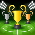 Soccer background with bright spot lights and three award trophy on gridiron Royalty Free Stock Photography