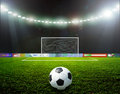 Soccer bal football ball on green stadium arena in night illuminated bright spotlights Stock Photography