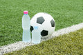 Soccer ball and bottles of cold wate water on field Royalty Free Stock Photo