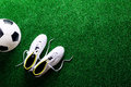 Soccer ball and cleats against green artificial turf, studio sho Royalty Free Stock Photo