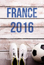 Soccer ball, cleats and France 2016 sign, studio shot. Royalty Free Stock Photo