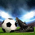 Soccer ball and cleats in grass Royalty Free Stock Photo