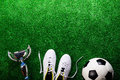 Soccer ball, cleats and trophy against green artificial turf Royalty Free Stock Photo