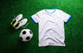 Soccer ball,cleats and white t-shirt against artificial turf Royalty Free Stock Photo