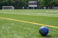 Soccer ball on field with teams, goal, scoreboard in background Royalty Free Stock Photo