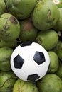 Soccer ball football resting with fresh green coconuts on a pile of drinking coconut coco verde gelado in rio de janeiro brazil Royalty Free Stock Photos