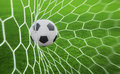 Soccer ball in goal with green background Stock Photo