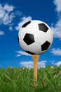 Soccer ball on golf tee Stock Image