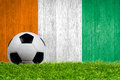 Soccer ball on grass with ivory coast flag background close up Stock Images
