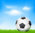 Soccer ball on grass over sky with clouds background Royalty Free Stock Photo