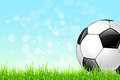 Soccer ball on green grass background and blue sky Royalty Free Stock Photo