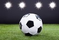 Soccer ball on green pitch with lights in background Stock Image