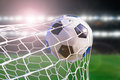 Soccer ball hit the net success goal concept on stadium light background Royalty Free Stock Photo