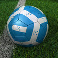 Soccer ball with honduras flag d on green field Stock Image