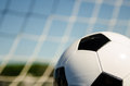 Soccer ball with netting image of on grass close up blue sky and Royalty Free Stock Photos