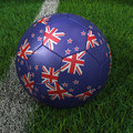Soccer ball with new zealand flag d on green field Royalty Free Stock Image