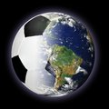 Soccer ball and planet earth merged together concept of dominating our world with million players in over countries is the most Royalty Free Stock Photo