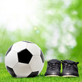 Soccer ball and soccer boots lying on the playground Royalty Free Stock Photography